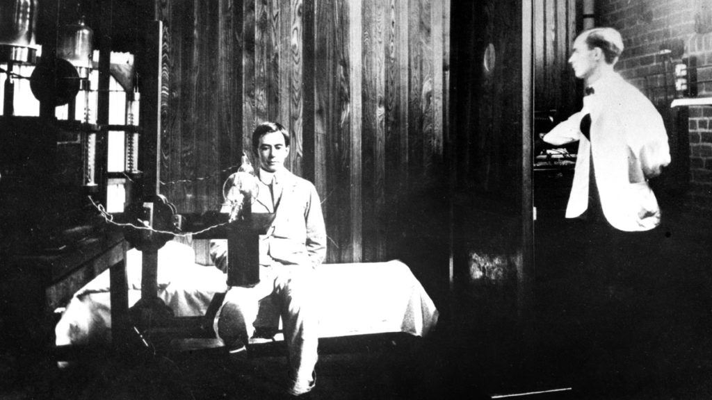 man sitting on bed with leg lifted under table with tube while on left man without hand stands behind wooden partition