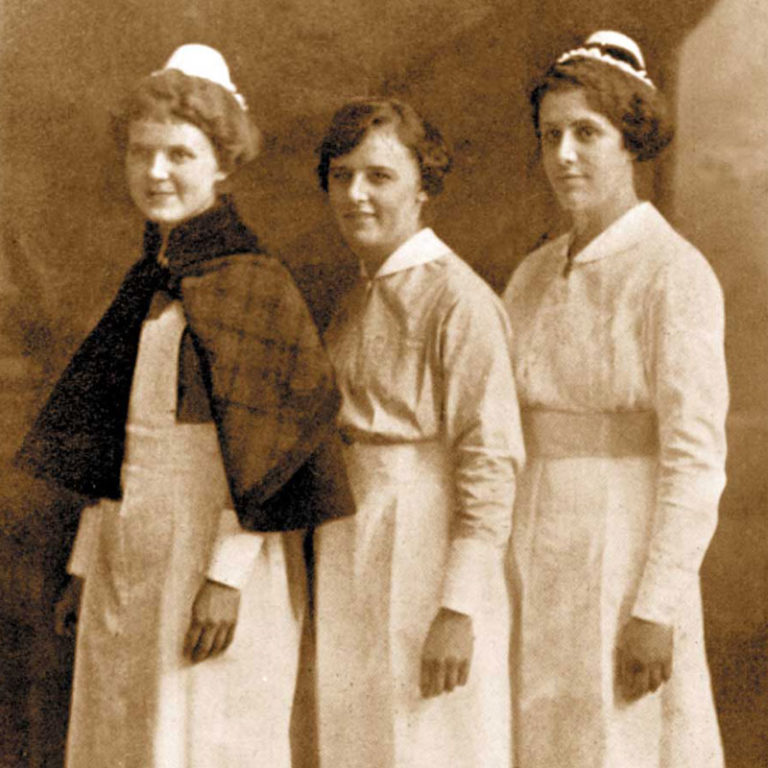three women wearing nursing uniforms; on right, white cap and cape; middle, without cap; on left with cap with black ribbon