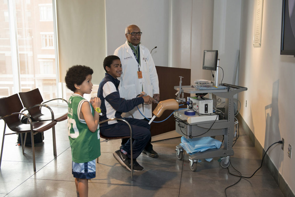 Teen boy demontrates minimally invasive knee surgery while older man and young boy look on in MGH Museum