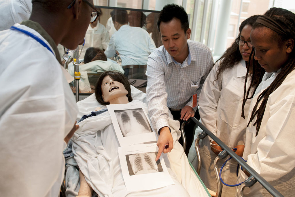 Simulation mannequin lies on a table while man points to xray scans and three people look on