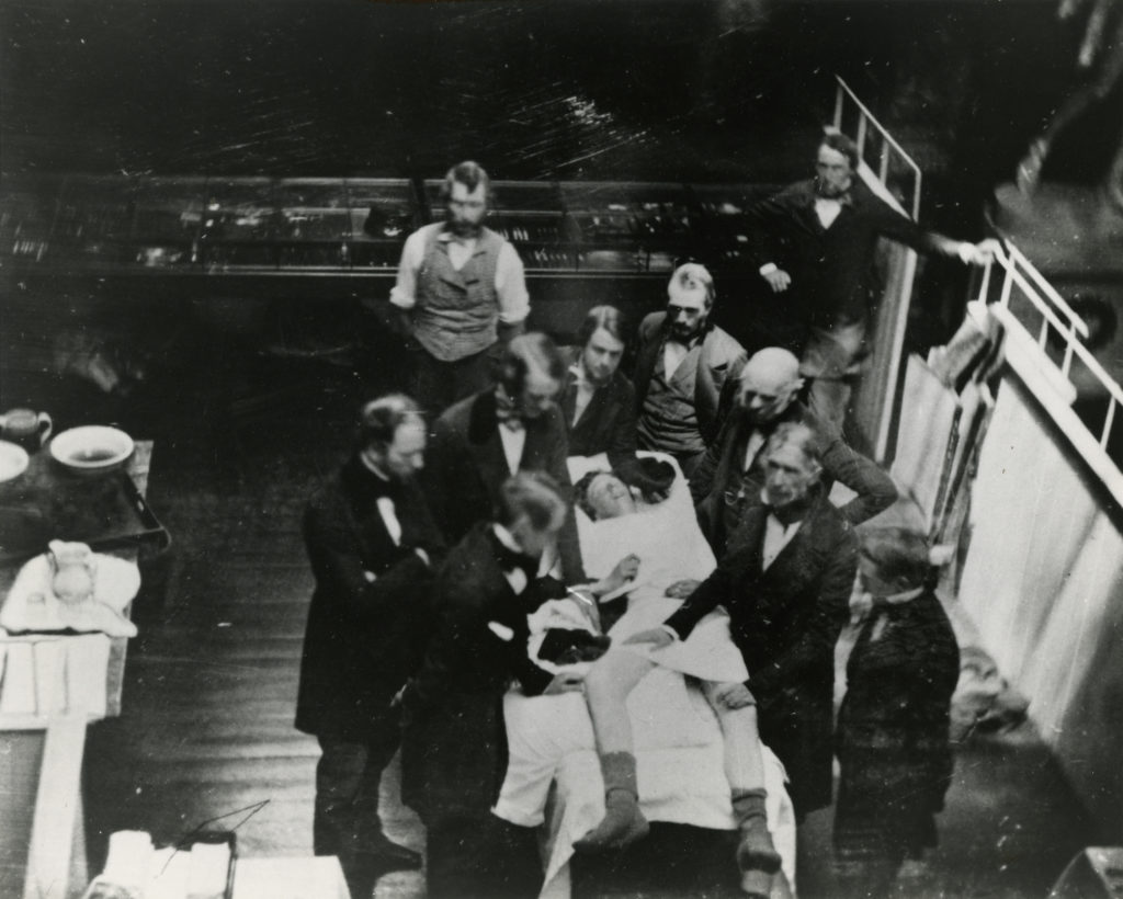 1847 B&W daguerreotype photo of an operation under ether with man on right placing hands on the legs of patient